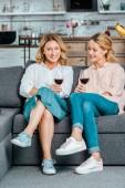 Fotografia madre matura e figlia adulta con bicchieri di vino rosso, trascorrere del tempo insieme sul divano a casa