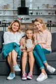 Fotografie dítě s matkou a babičkou seděli na gauči a sledování televize u vás doma