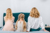 Fotografie rear view of child with mother and grandmother sitting on bed at home