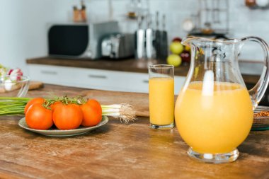 close-up shot of raw tomatoes with leek and jug of orange juice on table at modern kitchen