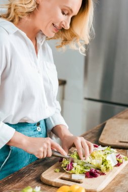 close-up shot of happy adult woman cutting lettuce for salad at kitchen