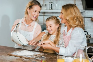 Happy child with mother and grandmother pouring flour through sieve during dough preparation at home stock vector