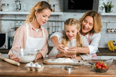 happy laughing child with mother and grandmother making dough with flour and egg together at home