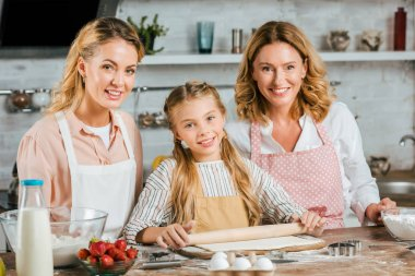 Beautiful smiling three generations of women making dough together at home and looking at camera stock vector