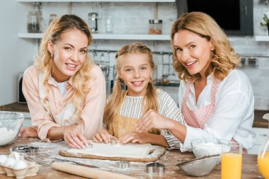 beautiful happy three generations of women making dough together at home and looking at camera