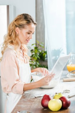 attractive young woman making dough and using tablet at home