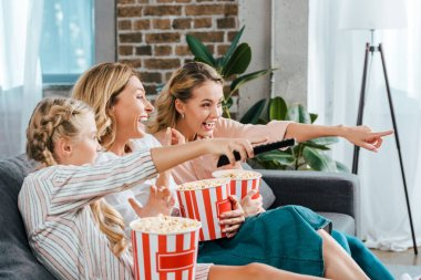 Excited child with mother and grandmother watching movie on couch at home with buckets of popcorn and pointing at screen stock vector