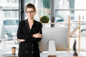 Fotografie portrait of attractive businesswoman standing with crossed arms and looking at camera in office