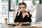 usmívající se atraktivní podnikatelka mluví stacionární telefonicky v kanceláři a ukazuje palec