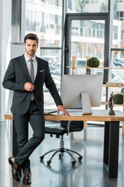 Handsome businessman standing near table in office and looking at camera stock vector