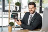 usmíval se pohledný podnikatel kalkulačka, u stolu v kanceláři a při pohledu na fotoaparát