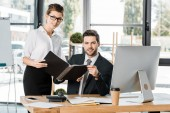 businesswoman and businessman holding folder with documents in office and looking at camera