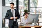 Fotografie pensive businessman standing at workplace with colleague in office