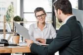 usměvavá podnikatelka a obchodní partner s doklady o práci na pracovišti v úřadu
