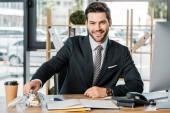 portrét usmívající se podnikatel dát peníze do zavařovačky s dovolenou nápis na pracovišti