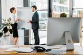 Fotografie Selektivní fokus se spolupracovníky diskutovat o práci na prázdnou bílou tabuli v úřadu