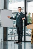 young smiling businessman in suit standing at empty white board in office