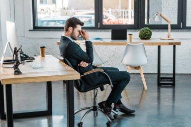 side view of tired businessman sitting on chair and touching nose bridge in office