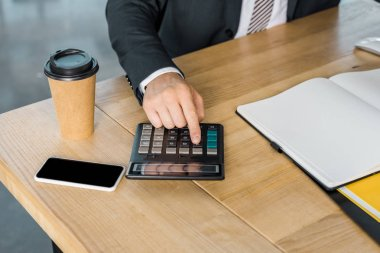 Cropped image of businessman using calculator during work in office stock vector