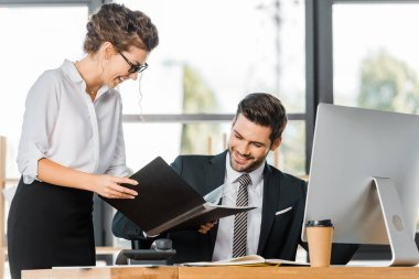 smiling secretary showing folder with documents to handsome businessman in office