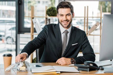 portrait of smiling businessman putting money into glass jar with vacation inscription at workplace