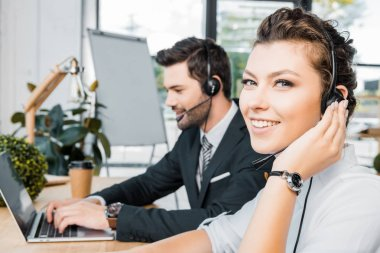 side view of smiling call center operators at workplace in office