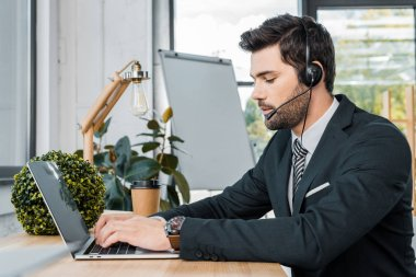 side view of male call center operator with headset working at workplace with laptop in office