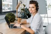mladá usmívající se žena call centrum operátor s mikrofonem na pracovišti v úřadu