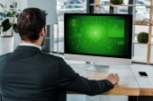 back view of businessman at workplace with computer screen with diagram in office