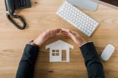 Fotografie Částečný pohled podnikatel pokrývající papírový model s rukama na pracovišti s klávesnicí a počítačová myš, pojištění koncept domu