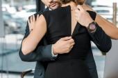 Fotografie Teilansicht der Geschäftsmann entpacken Dress der verführerische geschäftsfrau im Büro