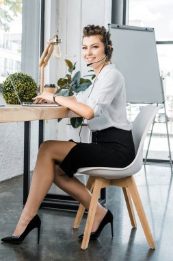 Young smiling female call center operator with headset at workplace in office stock vector