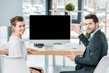 Young smiling business colleagues at workplace with blank computer screen in office stock vector