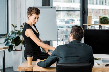 young businesswoman flirting with colleague at workplace in office