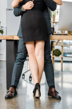 cropped shot of businessman unzipping dress of seductive businesswoman at workplace in office