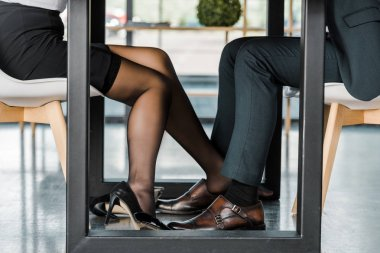 cropped shot of businesswoman flirting with businessman during work in office