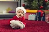 Nahaufnahme Porträt eines entzückenden kleinen Babys im Weihnachtsanzug, das auf dem roten Teppich mit Teddybär vor Weihnachtsbaum und Geschenken liegt
