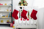Fotografie gift socks hanging on infant bed with little baby in santa suit inside