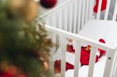 Fotografia piccolo bambino adorabile nel vestito della santa che si trova nel presepe con albero di Natale su primo piano