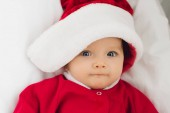 close-up portrait of adorable little baby in santa suit lying in bed and looking at camera