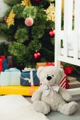 Fotografie teddy bear leaning on cradle in front of christmas tree and gifts