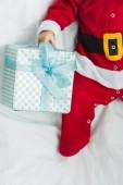 Fényképek levágott lövés a kisbabát a santa ruha fekve gyerekágy karácsonyi ajándék
