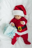 pohled shora na rozkošné miminko v santa obleku ležet v postýlce s vánoční dárek