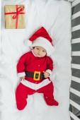 pohled shora na šťastné děťátko v santa obleku ležet v postýlce s vánoční dárek