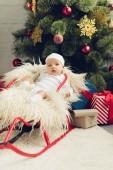 entzückende kleine Baby in Schlitten vor Weihnachtsbaum mit Geschenken