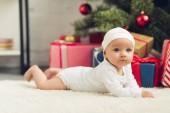 adorable little baby lying on floor with christmas gifts