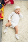 Fotografie adorable little baby lying on floor with gift boxes