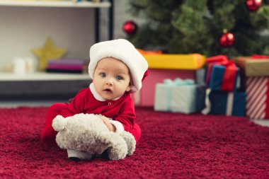 Close-up portrait of beautiful little baby in santa suit lying on red carpet with teddy bear in front of christmas tree and gifts and looking at camera stock vector