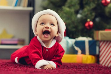 close-up portrait of laughing little baby in santa suit lying on red carpet in front of christmas tree and gifts