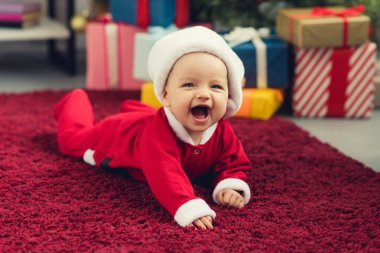 Laughing little baby in santa suit lying on red carpet in front of christmas tree and gifts stock vector